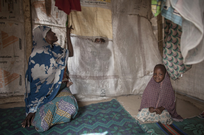 Hamsatu peeks through a tear in her tent while holding daughter Hauwa on her back as she sits next to Fatima, the 3-year-old foster daughter of Halima. Fatima was separated from her mother as they were trying to escape Boko Haram. (Jane Hahn/For The Washington Post)
