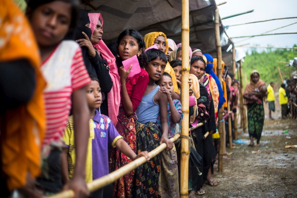 Rohingya women and children wait in a queue for an aid distribution at Kutupalong refugee camp in Cox's Bazar, Bangladesh.  © UNHCR/Roger Arnold
