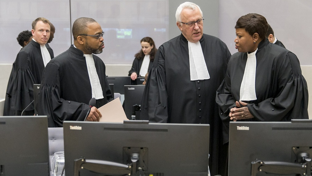 Jean-Jacques Badibanga, James Stewart, and Chief Prosecutor Fatou Bensouda are seen in a court room of the ICC before the delivery of the judgment in the case of Jean-Pierre Bemba in the Hague, 2016. REUTERS/Jerry Lampen