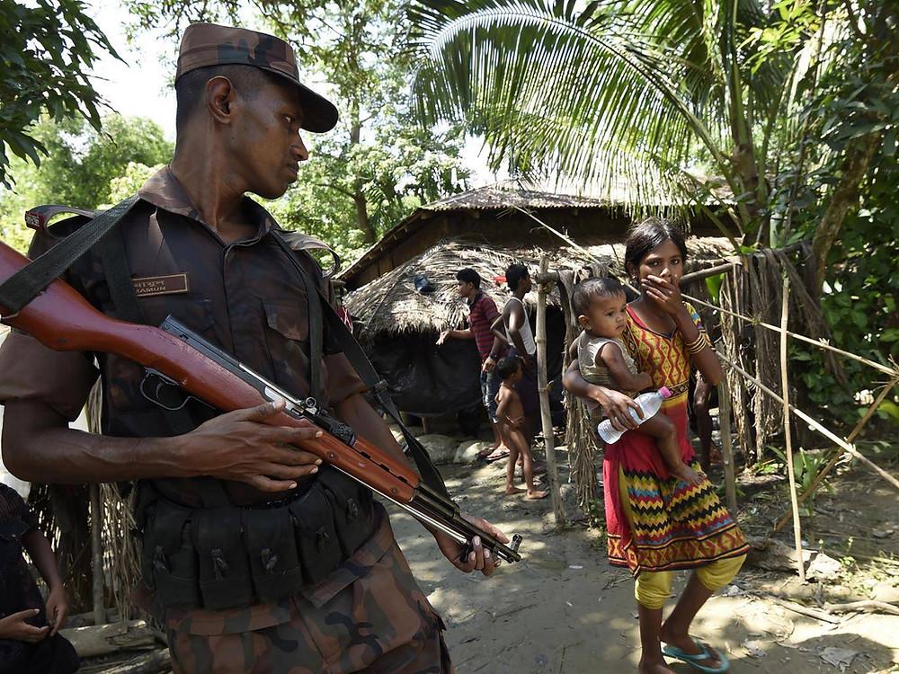 Refugees pass a Bangladeshi border guard at a camp in the no-man's land area between Burma and Bangladesh, near Gumdhum village in Ukhia (AFP/Getty)