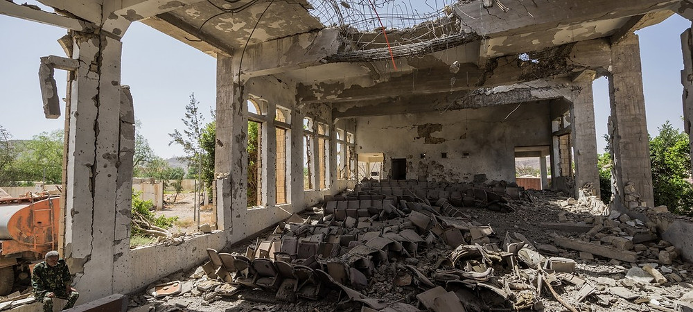 Giles Clarke/UN OCHA A military guard sits in the former Assembly Hall of the Governor of Saada, which now lies in ruins. Since the Yemen conflict escalated two years ago, much of the city's infrastructure has been destroyed.