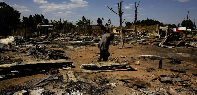 A man walks through ruins of an area of Chepilat in the Rift Valley Province, February 2008. The burning of homes by Kalenjin men, forced residents of both the Kisii and the Kikuyu ethnic groups to flee. © 2008 Marcus Bleasdale/VII