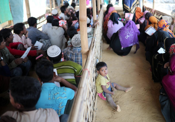 A Rohingya child sits on the floor while his mother waits in a queue to collect aid supplies in Kutupalong refugee camp in Cox's Bazar, Bangladesh, January 21, 2018. REUTERS/Mohammad Ponir Hossain