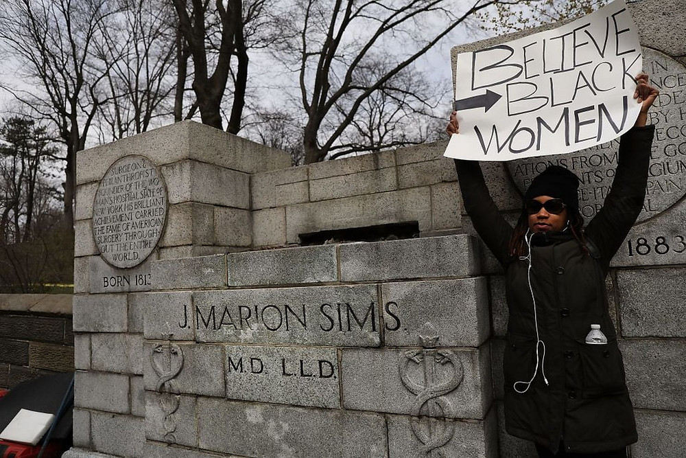 A woman stands beside the pedestal where a statue of James Marion Sims was taken down in New York City on April 17. (Spencer Platt/Getty Images)