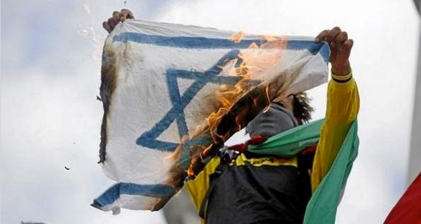 A pro-Palestinian demonstrator holds up a burning Israeli flag on the Republique square in Paris, during a banned demonstration against Israel's military operation in Gaza and in support of the Palestinian people, on July 26, 2014. (KENZO TRIBOUILLARD/AFP/Getty Images)