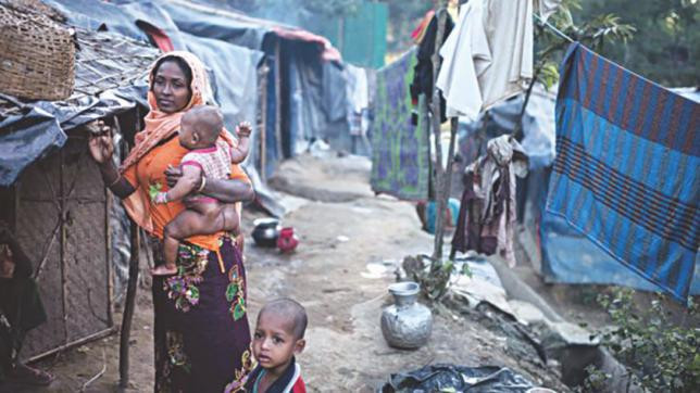 A Rohingya woman and child stand in the Naybara refugee camp in Cox's Bazar, December 3, 2017. PHOTO: AFP