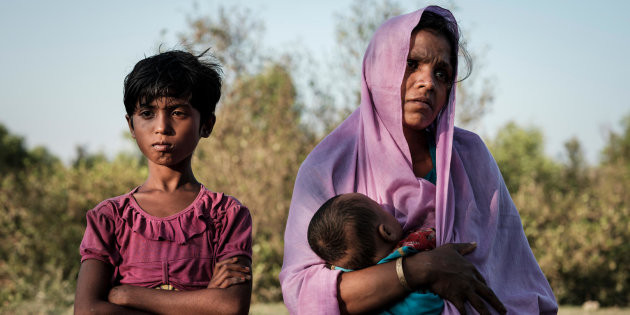 Rohingya refugee Mariom Khatun, 25, holds her baby Firuz Ahmed, 5 months, as they rest on the banks of the Naf River following a six-hour ordeal crossing the river on a makeshift raft made of bamboo and empty plastic oil containers tied together with rope, in Cox's Bazar District, Bangladesh.