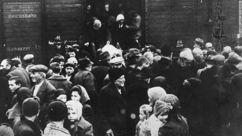 Jews deported from Hungary exit a German boxcar onto a crowded railway platform at Auschwitz concentration camp, Poland, in 1944.