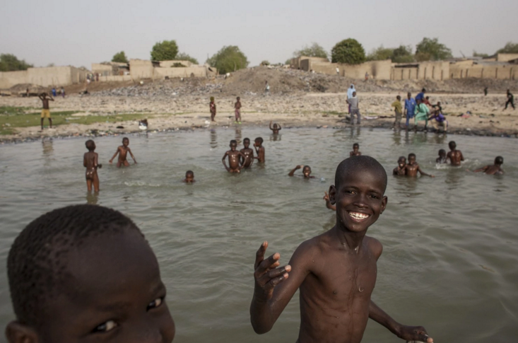 Children play by the river in Maiduguri, Nigeria. In many Nigerian communities, people believe that the father's blood profoundly influences his offspring, so the children conceived through rapes by Boko Haram fighters face rejection. (Jane Hahn/For The Washington Post)
