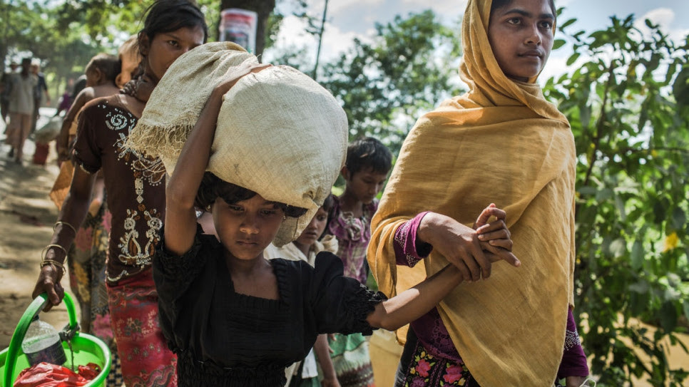 Eighteen-year-old Rabiaa Khatun and her niece, Umme Salma, 8, walk 10 kilometres from the Myanmar border to a UNHCR transit camp in Kutupalong, Bangladesh.  © UNHCR/Andrew McConnell