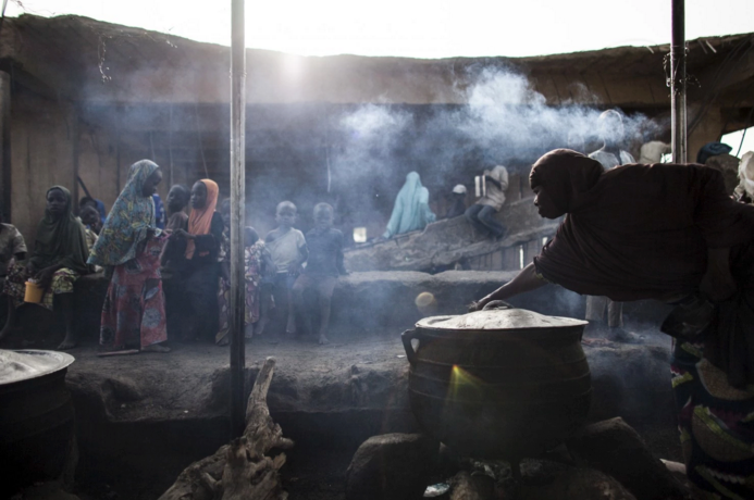 A woman prepares food at the children's kitchen at the Dalori camp. It holds close to 20,000 people and is administered by the Ni­ger­ian military, which regularly questions the refugees about their loyalties. (Jane Hahn/For The Washington Post)
