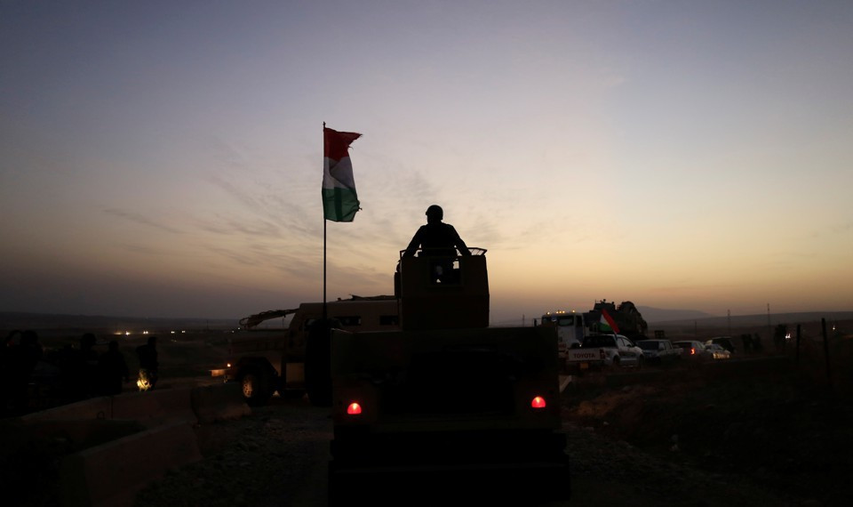 A Kurdish Peshmerga fighter looks over as he stands on the top of a humvee in front of an Islamic State militants' position outside the town of Naweran near Mosul. (REUTERS/Zohra Bensemra)
