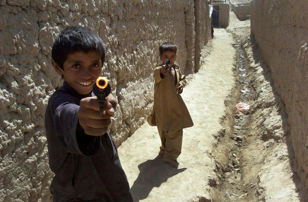 Boys playing with toy guns run into a village alley in Bagram, Afghanistan, 2009 (Photo: Flickr/UN Photo/Eric Kanalstein)