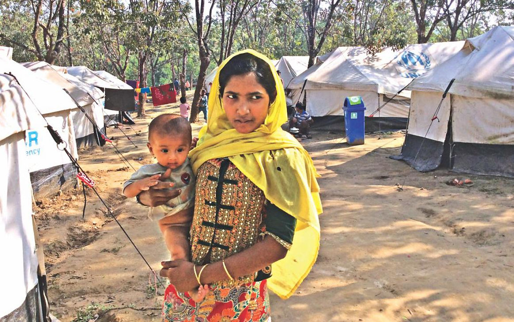Nur Fatima, a woman who along with 14 other Rohingyas arrived in Bangladesh on Thursday, with a neighbour's baby at a UNHCR temporary camp in Cox's Bazar's Balukhali yesterday. Photo: Pinaki Roy