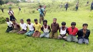 """[T]aken on the day the 10 Rohingya men were killed. Paramilitary police officer Aung Min, left, stands guard behind them. The picture was obtained from a Buddhist village elder, and authenticated by witnesses."" – Reuters Special Report"