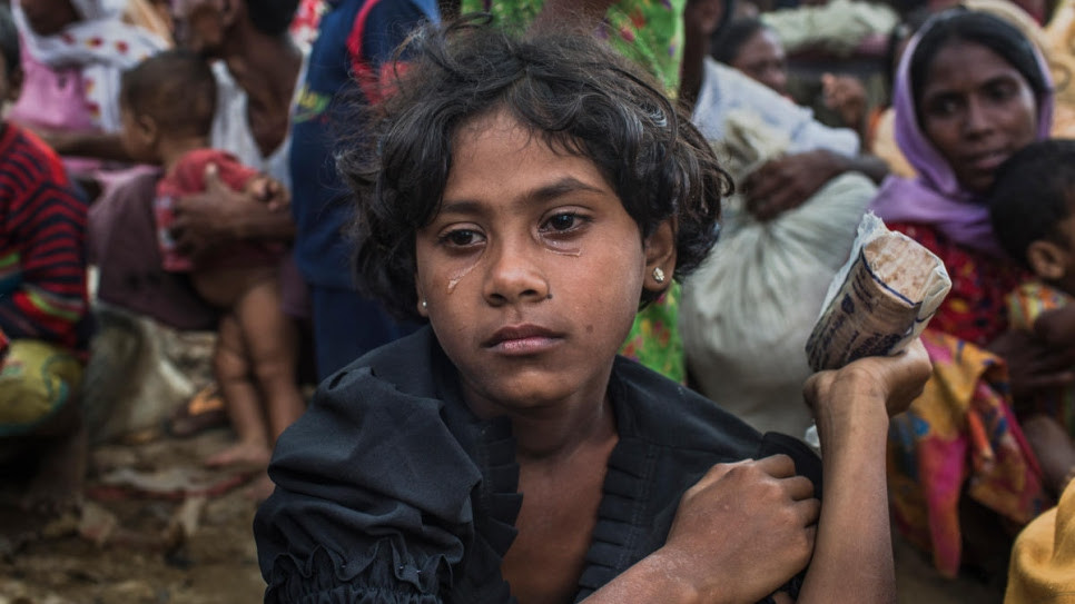 Umme Salma, 8, sits in tears after walking 10 kilometres from Myanmar to Kutupalong. Umme's parents were killed when their village was attacked. Both she and her sister are being cared for by their aunt, Rabiaa Khatun, who is 18. © UNHCR/Andrew McConnell