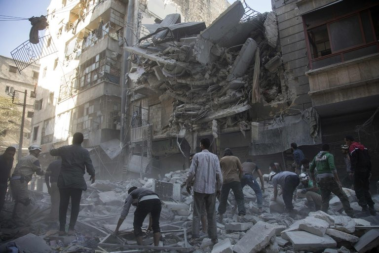 Civilians and rescuers at the site of an airstrike in Aleppo, Syria, on Tuesday. Credit Karam Al-Masri/Agence France-Presse — Getty Images