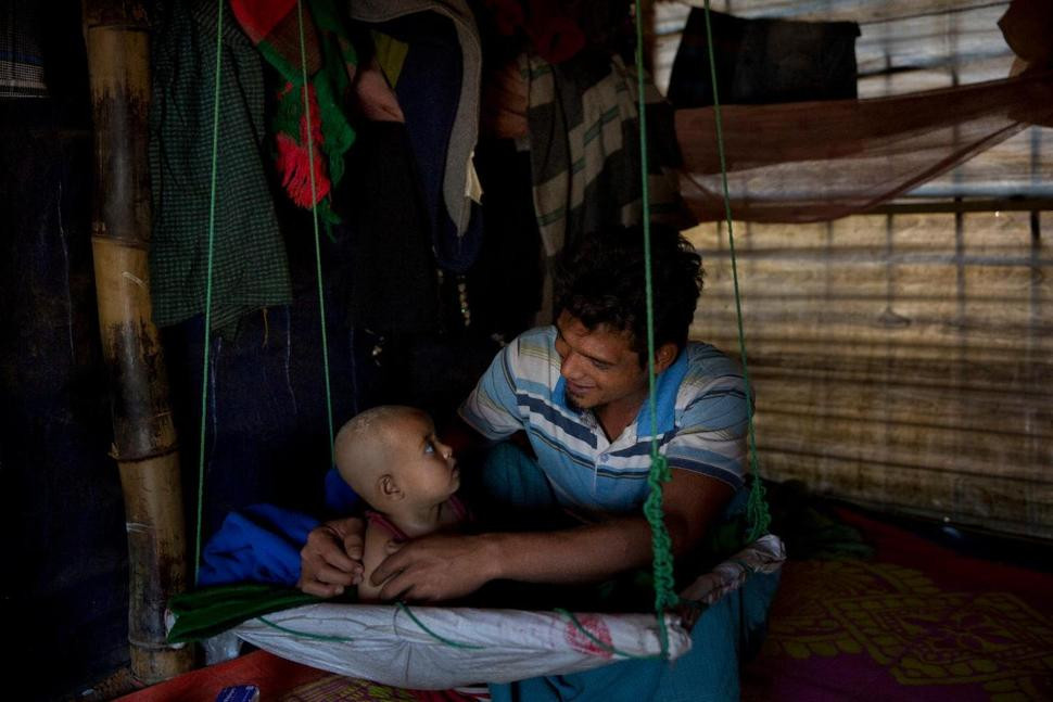 In this Jan. 21, 2018 photo, Rohingya Muslim refugee Noor Kadir, 24, from the Myanmar village of Gu Dar Pyin, plays with his son inside the family makeshift shelter in Balukhali refugee camp, Bangladesh. The Associated Press has confirmed more than five previously unreported mass graves in the Myanmar village of Gu Dar Pyin through multiple interviews with more than two dozen survivors in Bangladesh refugee camps and through time-stamped cellphone videos. Survivors said that the soldiers carefully planned the Aug. 27 attack, and then deliberately tried to hide what they had done. They came to the slaughter armed not only with rifles, knives, rocket launchers and grenades, but also with shovels to dig pits and acid to burn away faces and hands so that the bodies could not be identified. Kadir and 14 others, all Rohingya Muslims in the Myanmar village of Gu Dar Pyin, had been choosing players for the soccer-like game of chinlone when the gunfire began. They scattered from what sounded like hard rain on a tin roof. By the time the Myanmar military stopped shooting, only Kadir and two teammates were left alive. (AP Photo/Manish Swarup) The Associated Press
