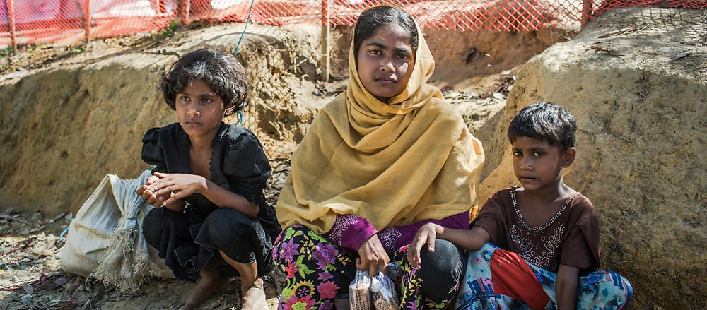 Eighteen-year-old Rabiaa Khatun and her nieces, Umme Salma, 8, and Noor Kalima, 4, rest after walking 10 kilometres from the Myanmar border to a UNHCR transit camp in Kutupalong, Bangladesh. © UNHCR/Andrew McConnell