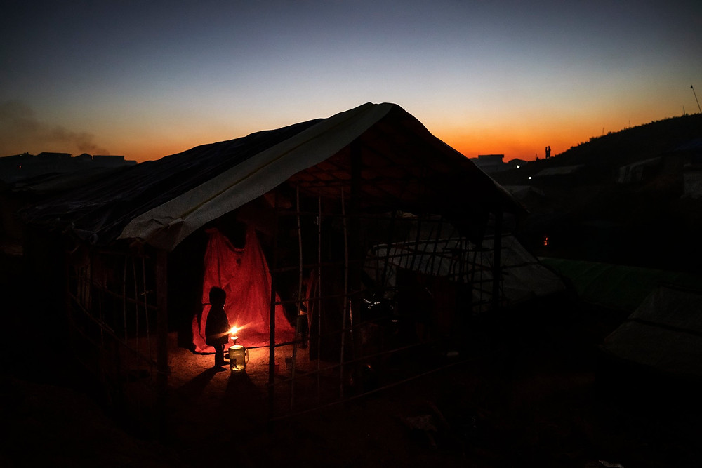 A Rohingya child in her family's tent at dusk in the Kutupalong camp in November. Credit Adam Dean for The New York Times