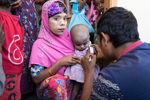 © UNICEF/Thame A Rohingya woman holds her little girl as her upper arm is measured to determine whether she is malnourished at a UNICEF-supported outpatient nutrition center in Thae Chaung village in Central Rakhine, Myanmar.