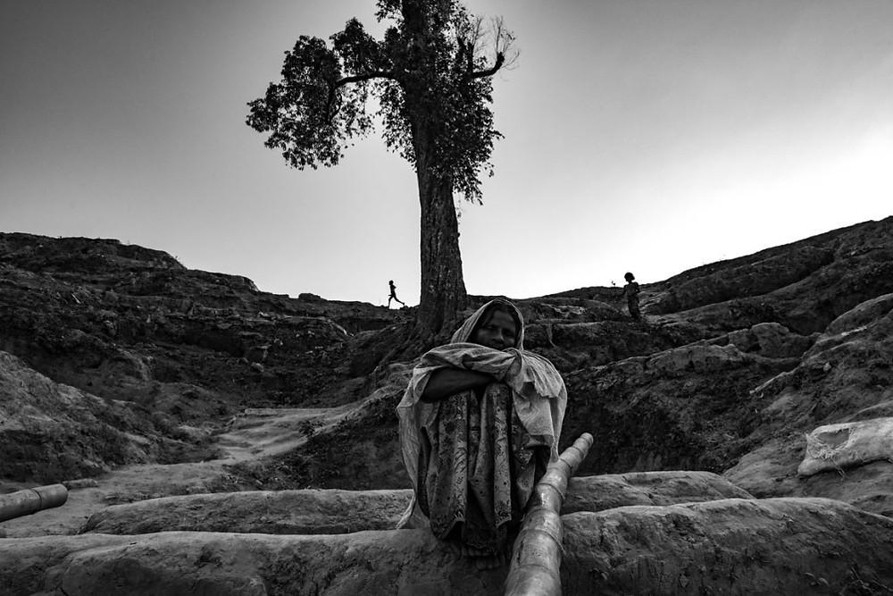A Rohingya woman rests near the Jamtoli refugee camp in Cox's Bazar, Bangladesh. | Szymon Barylski for Politico Magazine