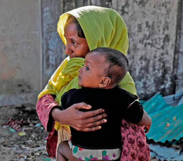 A Rohingya refugee woman holds her child after they crossed the Myanmar-Bangladesh border on Christmas Day. Photo: Reuters/Marko Djurica