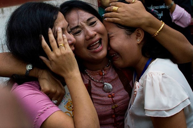Family members of Mr. Kyaw Soe Oo outside the court in Yangon on Wednesday. Credit Ye Aung Thu/Agence France-Presse — Getty Images