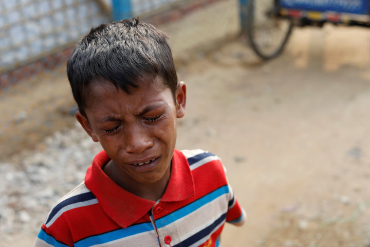 TYRONE SIU / REUTERS  A young Rohingya boys cries outside a hospital in the Kutupalong refugee camp after learning his father was killed, Jan. 13, 2018.