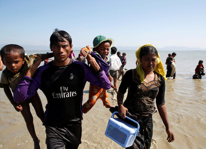 NAVESH CHITRAKAR / REUTERS  A Rohingya refugee man holding children walks towards the shore as they arrive on a makeshift boat after crossing the Bangladesh-Myanmar border, at Shah Porir Dwip near Cox's Bazar, Bangladesh, Nov. 9, 2017.