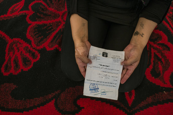 """Image: A 25-year-old Yazidi woman showed a """"Certificate of Emancipation"""" given to her by a Libyan who had enslaved her. He explained that he had finished his training as a suicide bomber and was planning to blow himself up, and was therefore setting her free. Credit Mauricio Lima for The New York Times"""