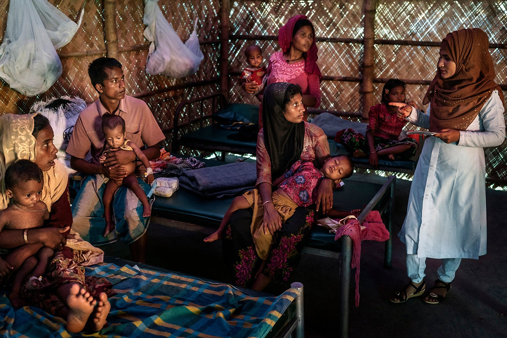 A doctor talking to parents and patients in the measles isolation ward of the Doctors Without Borders clinic in Kutapalong.CreditAdam Dean for The New York Times