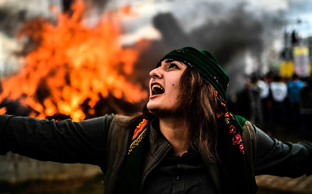 A Kurdish woman dances in front of a Newroz fire in Diyarbakir in March 2017. Photo: Bulent Kilic/AFP