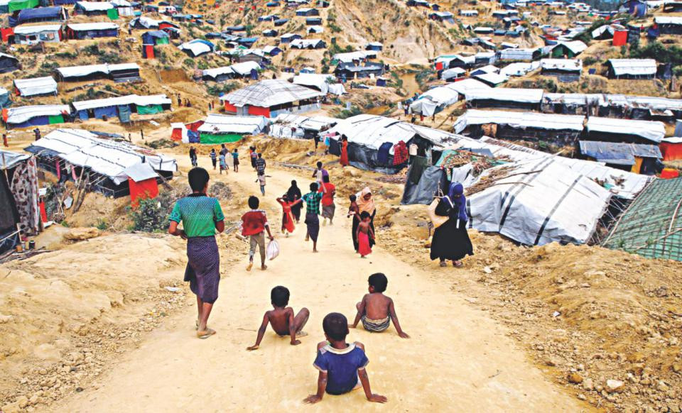 Rohingya refugee children slide down a road at Balukhali refugee camp near Cox's Bazar. PHOTO: REUTERS/Navesh Chitrakar