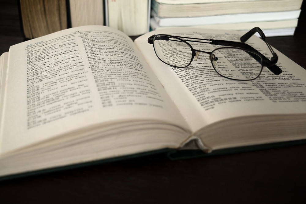 Picture showing an open dictionary with a pair of black glasses lying across one page.