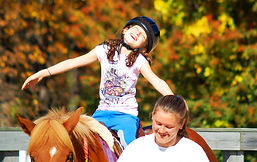 A Little Britches rider beams on the back of a copper pony, against a backdrop of fall foliage.