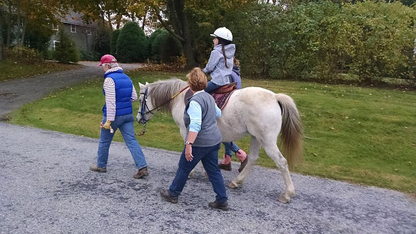 A Little Britches rider on a white pony, her therapist, and sidewalkers walk away from the camera.