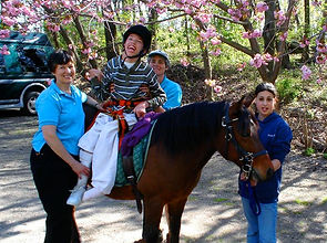 A Little Britches rider, surrounded by his sidewalker and therapists, grins from the back of a pony.