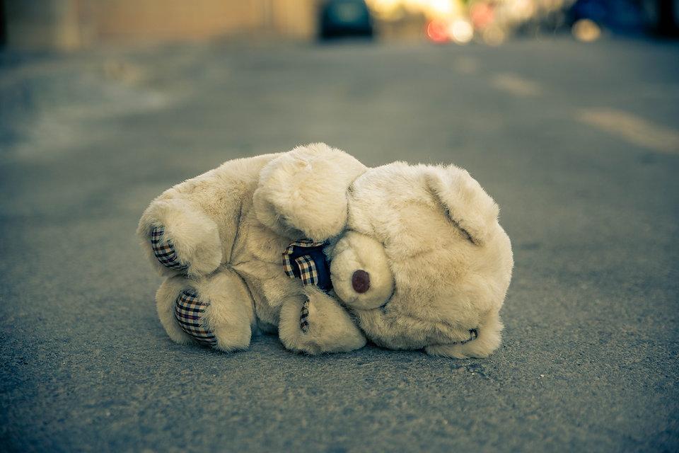 Teddy bear on the tarmac, sad, fragile
