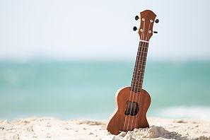 Guitar ukulele on sand beach with clear