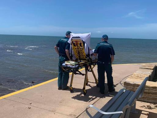 Dos paramédicos llevan a un paciente en camilla a ver el mar.