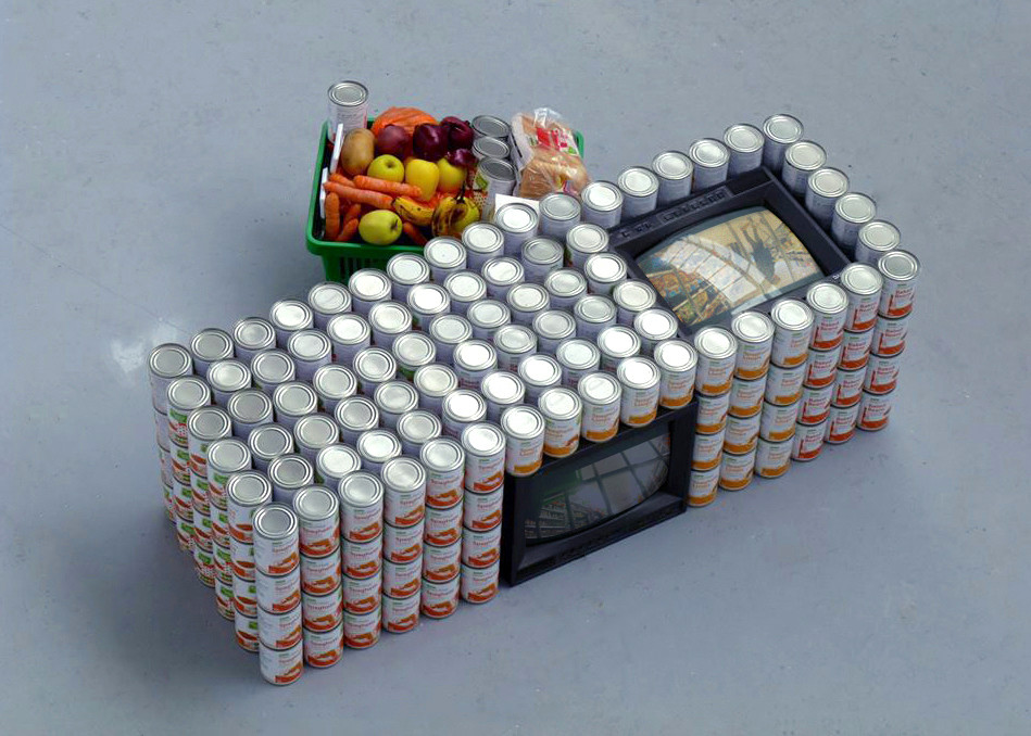 """A S D A   P R I C E  2 0 1 4  3 monitors, baked beans, spaghetti hoops, onions, carrots, bread, apples, oranges, potatoes and bananas.   D U R A T I O N     2 0 . 3 5  M I N U T E S 30  x  53  x  19 """"   This collaboration with Joanne Hooton situates 3 monitors in amongst numerous cans of beans. Hooton and I hid a camera in our shopping trolley and secretly filmed inside of Asda, Sainsbury's and Waitrose.   As the camera was hidden amongst our shopping during production, for this installation we proceeded to hide the monitors in stacks of our favourite tinned goods.   No beans were wasted in the making of this artwork; we ate them over the next two years."""