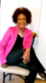 Rhonda sitting hot pink jacket white bac
