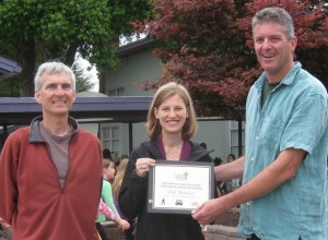 Mike McTighe presents award to Oak principal Amy Romem and WoW parent Doug Hahn