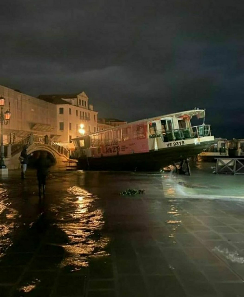 Foto noturna de um barco a deriva devido ao alagamento em Veneza
