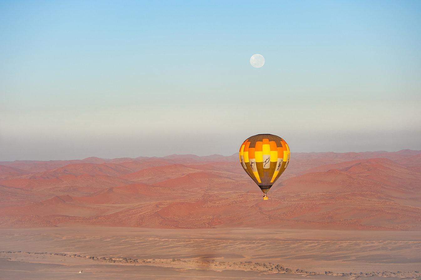 Ballontour bei Sonnenaufgang mit Vollmond in der Namib ©Johannes Ratermann