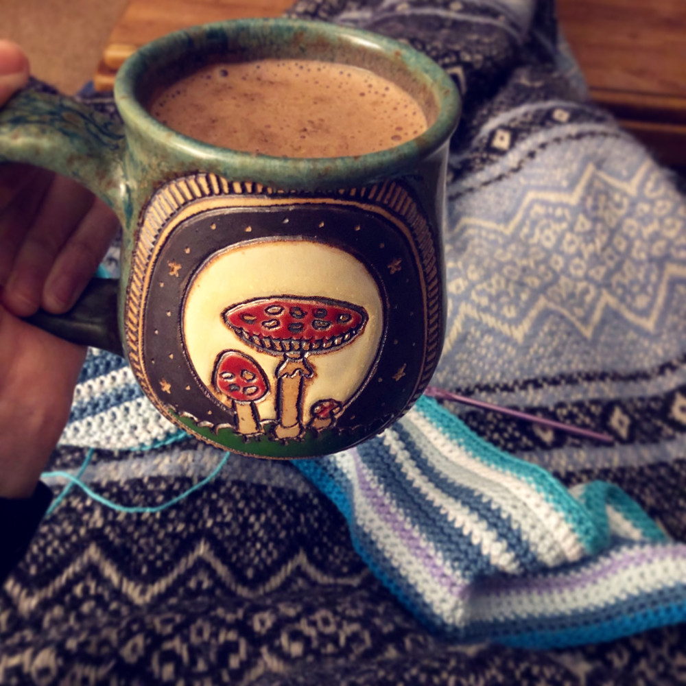 Image of a mug of hot cocoa. Mug has drawings of Fly Agaric mushrooms. In the background, a crocheted blanket can be seen, on top of a patterned blue and dark blue blanket.