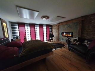 Schlafzimmer komplett von Assig-Raum: Bodenaufbau, Parkettboden verlegt, Wandverblender Holz, beleuchtete Schieferplatte, Kaminofen, Neubau Bett, Bepolsterung Bettteil, Nachtlampen hängend designt und gebaut