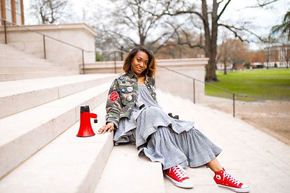 Image is a photo of Teryn sitting on steps with a grey dress, fatigue jacket, and red shoes.