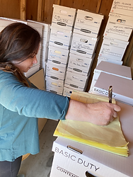 A woman writing on a notepad while she organizes a storage locker. Klutter Kutters Santa Barbara Clutter Cutters Moving Clients Move Managers Professional Organizer Senior Move Manager Move Manager Need Help Moving
